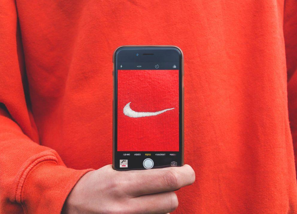 personne tenant un smartphone devant son pull avec le logo Nike